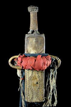 La lame reprend la forme des couteaux d'exécution que l'on trouve chez les Bamiléké et les Bamoun : base étroite allant en s'élargissant pour en augmenter le poids lors de la décapitation de prisonniers. La forme de l'étui se retouve aussi chez les Bamiléké. Toutefois cette arme à été collectée en pays Bamoun et faisait partie d'objets de lignage de la chefferie. Vous noterez le manche très ouvragé en bois et perles longues.