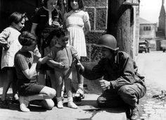 W.W. II, c.1944, A WAC (Women's Army Corp) dressed in field gear, helmet included, gives children candy.