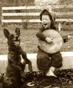 """Hit it doggie!"" Vintage Photo of dog making music with little girl."