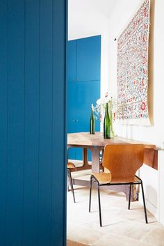 A blue kitchen with scarf/tapestry hanging above small table
