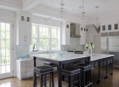 Traditional white kitchen with glass mosaic backsplash and marble counters.