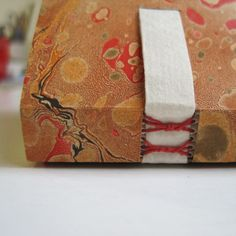 Book bound on paper tapes with marbled paper cover