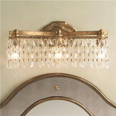 """a little fussy but I still like it Crystal Pendalogue Curtain Bath Light With a vintage gold finish and alternating crystal shapes, this 3 light vanity bath fixture is brimming with spirited splendor. UL damp location. 3x60 watts medium sockets. (9.25""""Hx18.5""""Wx5.75""""D)"""
