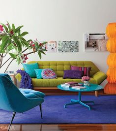 This living room shows secondary colors. the couch being blue, lamp orange, and the other couch being green..