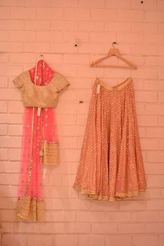 Peach lehenga with pink sheer dupatta and gold blouse
