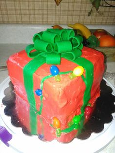 Christmas 2015  Present Cake   The most CHALLENGING cake I'd done up to that point.  I made the bow from fondant loop by loop. 3 layers Red & green velvet. Handmade edible lights  For more info, leave a comment