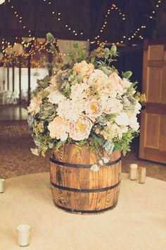 Floral arrangements a top of bourbon barrels. Love this