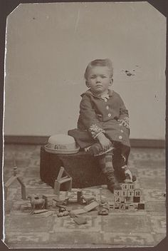 "Great CDV-sized tintype circa 1870 showing a boy with alphabet blocks and a variety of other 19th-century toys including what look like building blocks and wooden toy animals. The alphabet blocks have been built into a precarious pyramid which appears to read ""BE RTIE SK UNH"