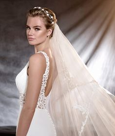 Exquisite gauze and tulle wedding dress, fitted to the hips, with a v neck and narrow straps. A delicate, flowing creation with a lovely decoration at the waist and an A-line skirt. An elegant, feminine option.