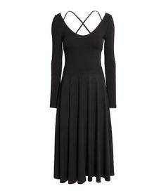 Black. Calf-length, fitted dress in thick jersey with a wide neckline, narrow straps crossed at back, and long sleeves. Seam at waist and circle skirt.