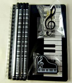 Piano keyboard stationery set. Pencils, notebook, eraser and musical note clip
