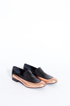 "Name: Rose Gold/Black Two-Tone Metallic Loafer • Designer: Jil Sander • Description: ""Two toned leather loafer with a rounded toe. Upper panel features black patent leather with rose gold beneath. Leather sole and insole. Rubber edging on heel. Dust bag included."" — ""Jil Sander Rose Gold/Black Two-Tone Metallic Loafer"", Totokaelo (Retrieved: 15 September, 2014)"