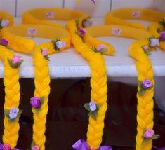 Tiara com a trança da Rapunzel, feita em lã amarela e decorada com flores e laço de cetim, com fio acabamento. Cumprimento total da trança = aproximadamente 90cm Pode ser utilizado como convite, acrescentando o rolinho do convite.