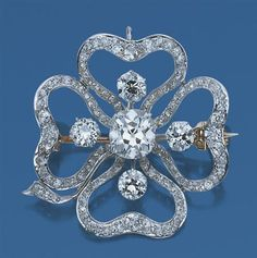 Diamond Flower Brooch   Platinum, gold, the openwork stylized four-leaf clover centering one cushion-shaped diamond* approximately 2.79 cts., quartered by 4 old European-cut diamonds approximately 2.00 cts., encircled by 4 scalloped petals set with 60 old-mine cut diamonds approximately 1.75 cts., circa 1905