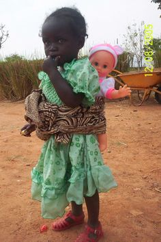 """a favorite toy -- in this photo an African girl plays """"mother"""" with her doll/baby wrapped up to her."""