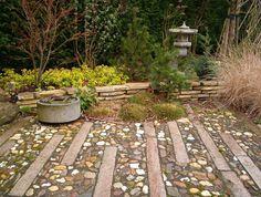 Winter in dit oosterse hoekje met japanse lantaarn (rankei) en waterbasin (tsukubai). De verharding bestaat uit graniet en maaskeien. www.houdijkstijltuinen.nl