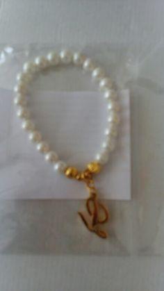 Pulsera personalizado de perlas del rio con dije de acero bañado en oro.