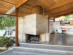 A large cinder-block fireplace rests half-in, half-out of the dining room in a renovated midcentury house in Los Angeles. Photo by Spencer Lowell. This originally appeared in Modern Renovation of a Midcentury House in Los Angeles. Fireplace Design, Fireplace Ideas, Open Fireplace, Los Angeles Homes, Bungalows, Dining Area, Dining Room, Midcentury Modern, Hearth