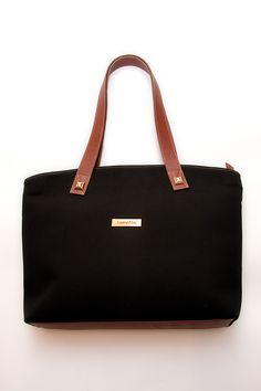 Shopping Bag de color negro, fabricado en tejido, con detalles de asas y base del bolso en piel 100% vacuno. Detalles de tachas y placa metálica en dorado.