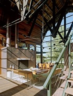 """The screened boathouse serves as an """"outdoor"""" living space. The New York-based design firm Stonefox worked with the couple, who collect modern and Minimalist art, to integrate their pieces into the house. A stainless-steel-and-spun-aluminum ceiling fixture, by David Weeks, mobilizes with the wind off the lake."""