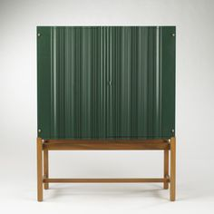 Lot 513: Josef Frank. cabinet, model #2192. 1954, painted wood, wood, brass. 43½ w x 18 d x 55½ h in. result: $12,000. estimate: $7,000–9,000. Two door cabinet with carved fronts in original green lacquer and three internal shelves.