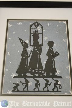 A piece of traditional cut-paper artwork featuring Saint Lucia, a Star Boy, a Baker, and the Tomptes
