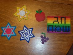 Homemade sukkah decorations.  Perler beads (the ones you melt together with an iron) from the craft store.  No colors running, no melting paper, hopefully durable!