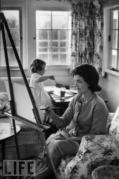 Jackie Kennedy paints with watercolors at an easel while Caroline paints a picture at home in 1960.