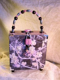 Cigar Box Purse - Chocolate Brown and Pink with Cherry Blossoms Motif, Pearl and Iridescent Accents    This cigar box purse was inspired by a beautiful scrapbooking paper I had with a cherry blossom motif. I ended up diffusing the image and making it even more unique by covering the paper with a delicate layer of white tissue paper, which softened the image of the cherry blossoms, and made it more abstract and ethereal.    I then embellished the design further by using dimensional paint and…