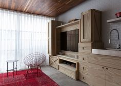 AP 1211 micro apartment in São Paulo by Alan Chu with storage space created by wooden crates and a black metal spiral staircase.