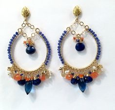 Blue Hoop Earring Gold Hoop Earring Blue Gemstone Chandelier Hoop Earring Colorful Statement Blue Lapis Beaded Boho Chandelier Ready to Ship    Large 14kt gold filled hoop earrings are wire wrapped with multi color gemstones of cobalt blue, orange and gold to create these glamorous, unique, handmade, chandelier hoop earrings.  Wire wrapped to add 14kt gold filled chain along the bottom, the earrings are centered by vibrant blue lapis briolettes that sparkle and anchor the earrings with their…