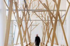 """Una foresta di rami popola la caffetteria del museo Città della Cultura della Galizia a Santiago de Compostela in Spagna. I tavoli sono disposti parallelamente sotto gli """"alberi"""" evocando la tradizione delle feste popolari. Il progetto è firmato Estudio Nómada."""