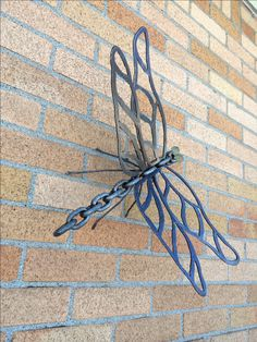 "Dragonfly sculpture skillfully welded out of reclaimed metal.  The head is from chain link with glass ball eyes, wings are filigree design plasma cut from 1/8"" plate steel, the body made from heavy chain link welded together and the legs from 1/8"" rod. The finish is an automotive grade clear coat. This one of a kind dragon fly would look beautiful in your garden, on a wall or in your home. Size: 14"" long x 20 ½""  x 7""tall. Weight 4.5 lbs"