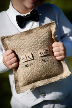 "Ring bearer pillow with ""we do"" in Scrabble tiles."