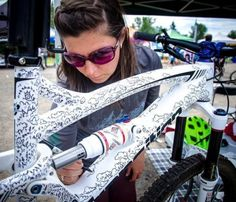 Photo of Helena Juhasz in North Vancouver, British Columbia, Canada. Helena Juhasz of North Shore Bike Shop works on the doodle art on her custom Transition during MEC Bike Fest in North Vancouver. Mountain Bike Stand, Mountain Bike Frames, Mountain Bike Shoes, Mountain Biking, Bicycle Paint Job, Bicycle Painting, Bicycle Art, Custom Paint Jobs, Bike Seat