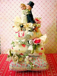 Ten inch tall 'cake' made of pin cushions to accommodate the vintage wedding topper. SO sweet and inventive. By Elizabeth Holcombe