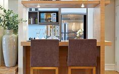 Outro espaço bem aproveitado foi a lateral da estante do living. A bancada de madeira não ocupa muito espaço e é ideal para refeições rápidas. Foto: Divulgação