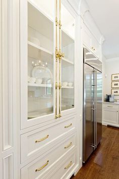 Gorgeous white kitchen is equipped with a stainless steel French door refrigerator inset beneath white cabinets accented with brass knobs.