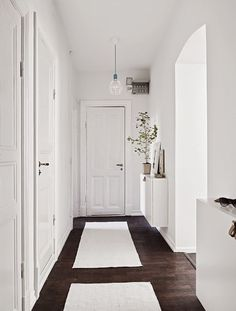 Struggling to decorate your long, narrow hallway? We have 19 long narrow hallway ideas that range in difficulty. From painting one wall to adding a long runner, we've got you covered. Turn your hallway into a library, or add shoe storage. All White Room, House Design, Small Entryways, White Hallway, Home, Tiny Entryway, Scandinavian Home, White Rooms, My Scandinavian Home