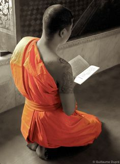 Young Buddhist monk praying at the Wat Kalayanamit.