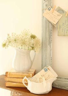Love the Queen Anne's lace bouquet, white pottery, postcards, books, painted frame... very pretty.