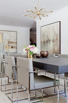 Chic, contemporary dining room features a brass and glass sputnik chandelier illuminating a wood and chrome dining table lined with gray leather dining chairs atop a gold and gray rug.