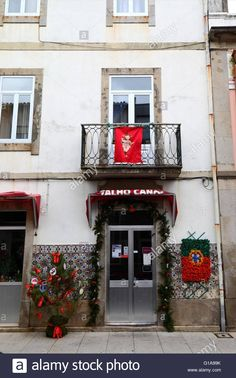 Christmas tree, red flag with baby Jesus and Portuguese flag outside shop entrance, Vila Praia de Ancora, Minho Province, northern Portugal Stock Photo