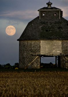 beautiful full moon behind a barn.