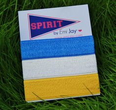 """Show your sporty side with our new """"Spirit by Emi-Jay"""" ponytail ties in Barefoot Blue, Yellow and White! These new ties are """"no line"""" to prevent folding and are perfect for that cute ponytail or to wear on your wrist! Find them at www.barefootac.com!"""