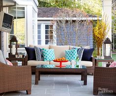 A stone tile floor and a handsome set of woven furniture take this porch into more formal territory, while charming accessories keep the look from becoming too stiff. Secret to Pretty: Pops of color are welcome even on a more formal porch. Using only two or three colors reinforces a sense of orderly design./