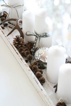 Love the white candles with simple grey ribbon, pinecones and a little bling