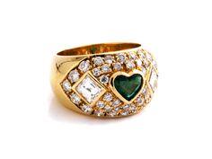 Ringweite: 54/ 55. Gewicht: ca. 11,9 g. GG 750. Bandring mit zentralem Smaragdherz, ca. 0,5 ct, zwei Diamanten im quadratischen Baguetteschliff, zus. ca. 1 ct,...