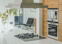 KVARTSIA, PUUTA JA LASIA  Kvartsi on kaunis ja kestävä tasomateriaali. Tähän persoonalliseen keittiöön asennettiin 60mm paksu valkoinen taso, joka tuo ryhtiä isoon tilaan.  Saarekkeen ympärille kokoontuvat niin vieraat kuin perheenjäsenetkin syömään, kokkaamaan, tekemään läksyjä ja töitä.   Keittiön ovet ovat zebraanoviilua ja vetimet lasia ja harjattua terästä. Yläovien materiaali on maitolasi, jota reunustaa alumiinikehys.