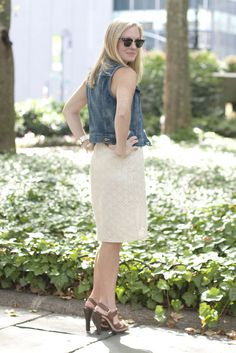 Kelley turns a country-inspired look into an office-appropriate outfit. A denim vest complements her off-white, lace dress, while a camel belt and stacked sandals help keep the look light and summery.